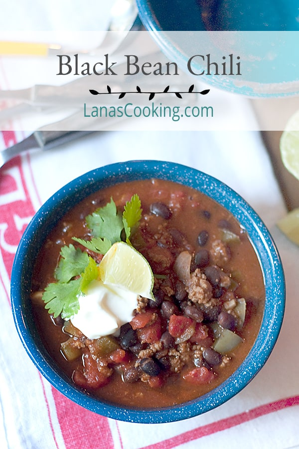 Black Bean Chili - a hearty, beefy chili rich with tomatoes, black beans, and spices. Top with sour cream and fresh cilantro. Pass lime wedges. From @NevrEnoughThyme https://www.lanascooking.com/black-bean-chili/