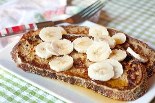 Banana Maple French Toast - whole grain French toast topped with sliced bananas and maple syrup. From @NevrEnoughThyme https://www.lanascooking.com/banana-maple-french-toast
