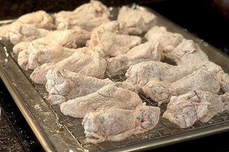 Coated wings on the rack inside the baking sheet.