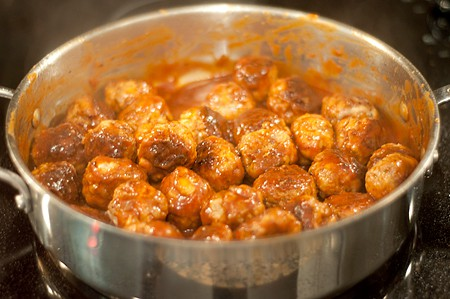 Meatballs added to sauce in skillet.