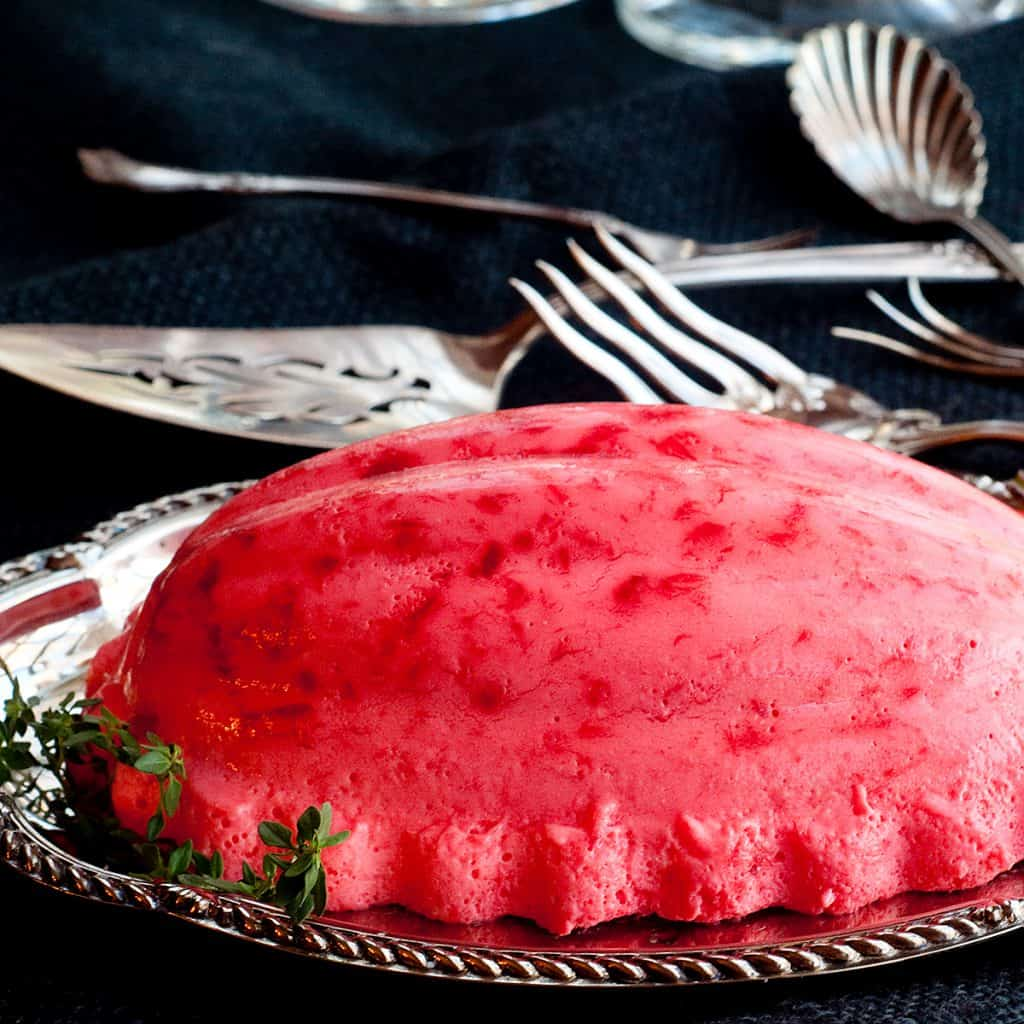 Raspberry jello mold on a silver serving tray with vintage serving pieces in the background.