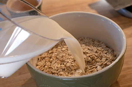 Combining oats, milk and orange juice in a mixing bowl.