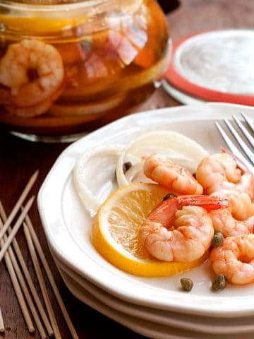 Pickled shrimp - Boiled shrimp layered with lemon slices, onion, and capers and marinated in cider vinegar. Serve with cocktail sauce on the side. https://www.lanascooking.com/pickled-shrimp/