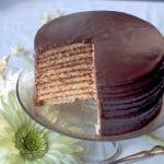 Chocolate Little Layer Cake sliced to reveal the layers presented on a glass cake plate.