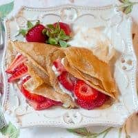 Strawberry Filled Whole Wheat Crepes - whole wheat crepes filled with fresh strawberries and lightly sweetened whipped cream. From @NevrEnoughThyme https://www.lanascooking.com/strawberry-filled-whole-wheat-crepes/