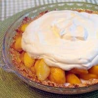 Heavenly Peach Pie with a sour cream filling in an almond and coconut pie shell. The perfect way to highlight delicious fresh peaches in season. From @NevrEnoughThyme https://www.lanascooking.com/heavenly-peach-pie/