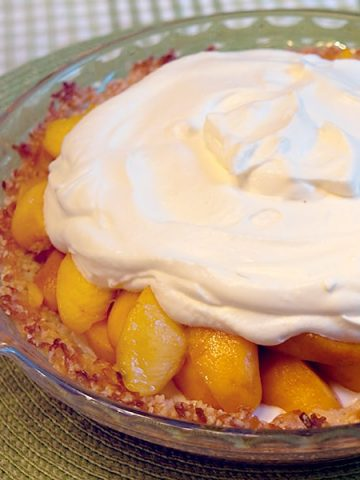 Heavenly Peach Pie with a sour cream filling in an almond and coconut pie shell. The perfect way to highlight delicious fresh peaches in season. https://www.lanascooking.com/heavenly-peach-pie/