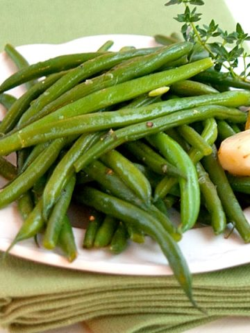 Braised Green Beans - very tender haricot verts braised in chicken stock and garlic, seasoned with olive oil and lemon juice. From @NevrEnoughThyme https://www.lanascooking.com/braised-green-beans/