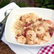 Mediterranean Shrimp with Angel Hair Pasta - shrimp in a sauce chock full of Mediterranean ingredients served over delicate angel hair pasta. https://www.lanascooking.com/mediterranean-shrimp-with-angel-hair-pasta/