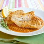 Pan Fried Fish with Red Pepper Sauce - an easy weeknight dinner of pan-fried fish served atop a sauce of roasted red peppers, tomatoes, and garlic. https://www.lanascooking.com/pan-fried-fish-with-red-pepper-sauce/