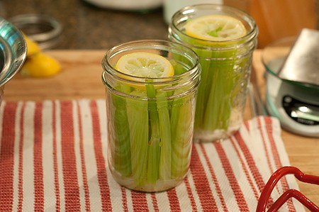 Two canning jars filled with celery sticks and lemon slices