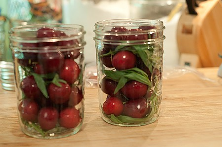 Two pint jars filled with cherries and tarragon