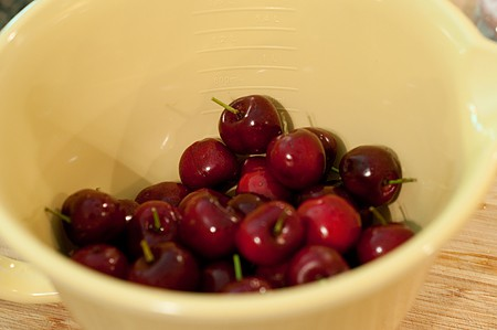 Yellow mixing bowl with red cherries