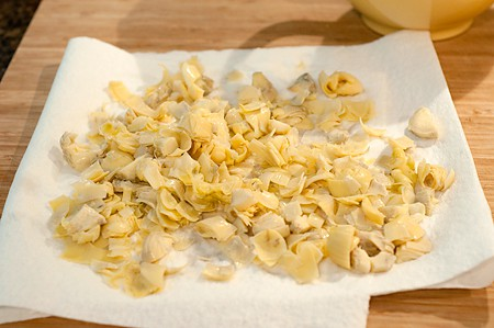 Draining chopped artichoke hearts