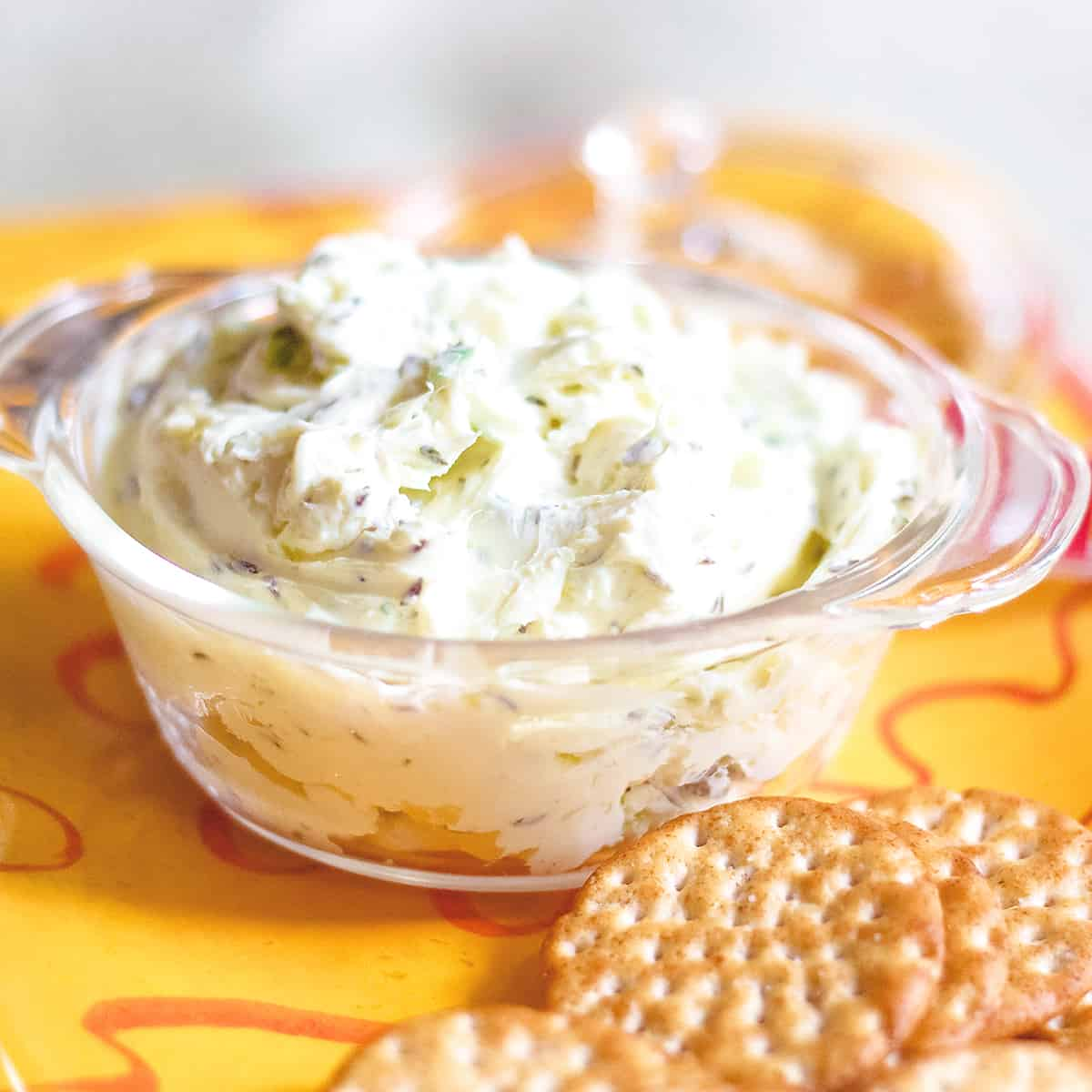 Caraway Cheese Spread in a glass serving bowl with crackers in the foreground.