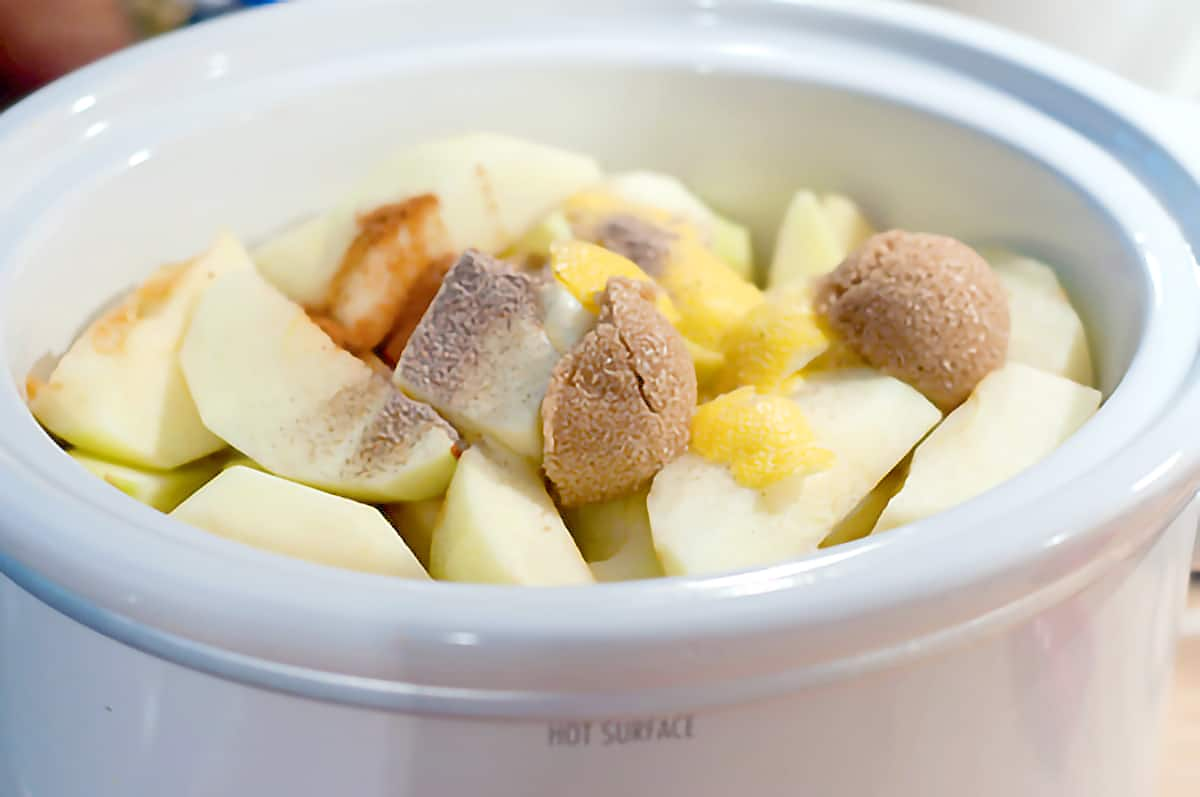 Slow cooker filled with apples, sugar, and spices.