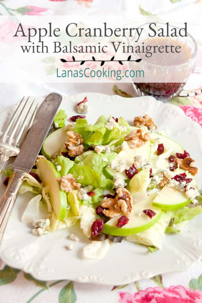 Apple Cranberry Salad on a white serving plate with vintage flatware and balsamic vinaigrette in a pitcher alongside. Text overlay for pinning
