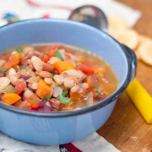 A bowl of mixed bean soup with a serving ladle alongside.