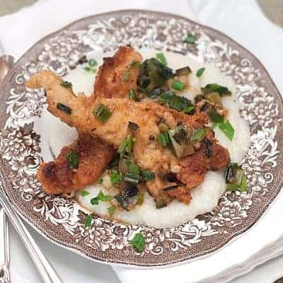 Chicken with Grits for a Cozy Winter Supper - Creamy, buttery grits topped with fried chicken strips and a green onion pan sauce. From @NevrEnoughThyme https://www.lanascooking.com/chicken-with-grits/