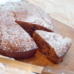 Irish Spiced Fruitcake on a serving board with a slice cut for serving.