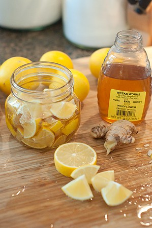 Assembling a jar of lemon, honey, and ginger cold and cough soother