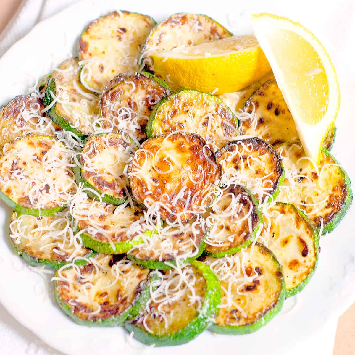 Pan Fried Zucchini with Lemon and Parmesan arranged on a serving plate.