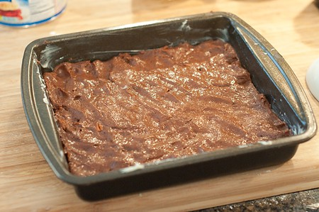 Pat the brownie batter into the pan with buttered fingers