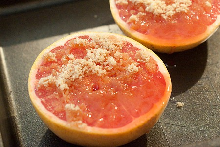 Grapefruit halves in a baking pan topped with sugar, butter, and cherry juice