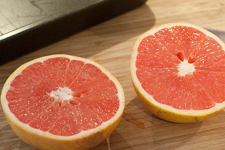 A halved grapefruit on a cutting board