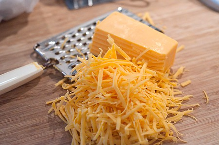 Grating cheese for Cheddar-Pecan Cheese Ring with Strawberry Preserves