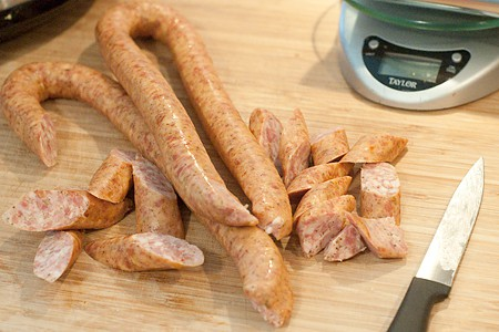 Cutting sausage into pieces on a board.