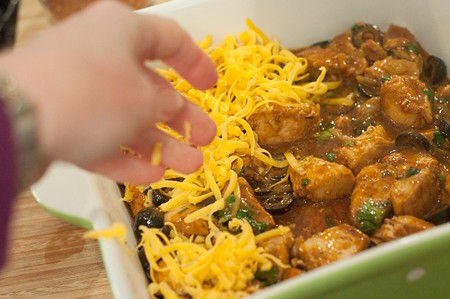 Topping the casserole with grated cheddar cheese.