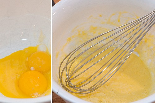 Egg yolks and a whisk in a mixing bowl.