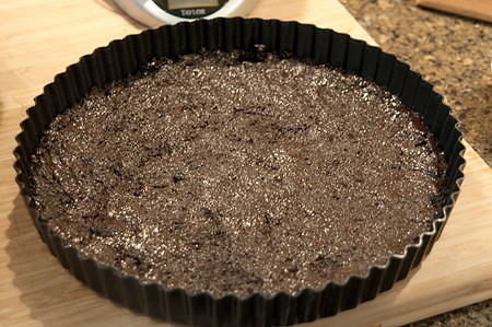 Chocolate cookie crust pressed into a tart pan.