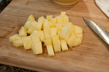 Fresh pineapple cut into bite-sized pieces with a knife on a cutting board