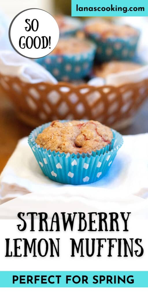 A strawberry lemon muffin sitting on a napkin with a basket of muffins in the background.