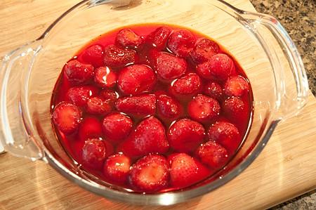 Strawberries and jello in a round dish.