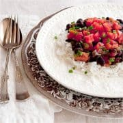 Black Beans and Rice with Ham - classic black beans and rice with the addition of tomatoes and ham. Garnished with fresh chopped tomatoes and chives. https://www.lanascooking.com/black-beans-and-rice-with-ham/