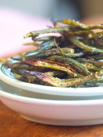 Crispy oven baked okra chips piled high in a white and green bowl.