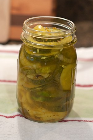 Filling canning jars with cucumbers, onions, and pickling liquid