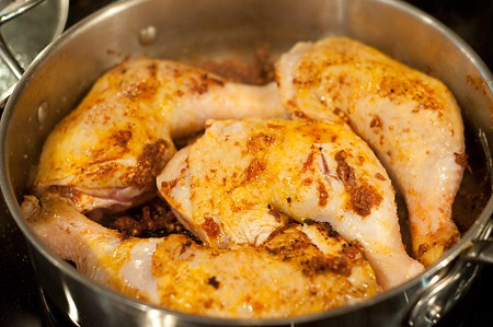Chicken quarters added to the skillet with spices.
