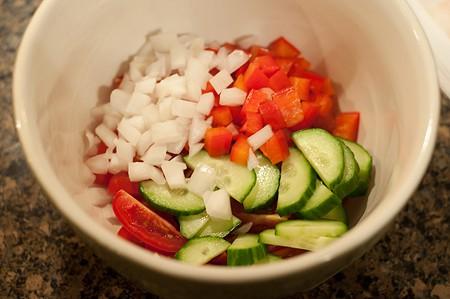 Preparing veggie garnish in a small bowl.
