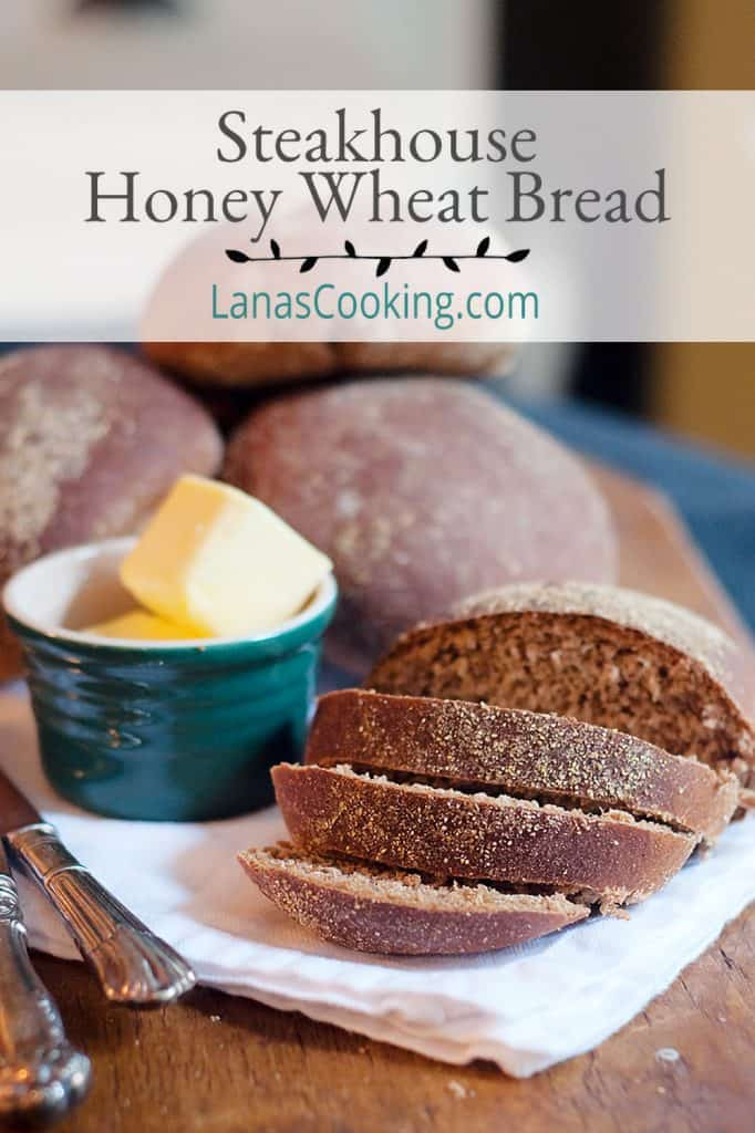 Steakhouse honey wheat bread sliced on a serving board with a napkin and a container of butter.