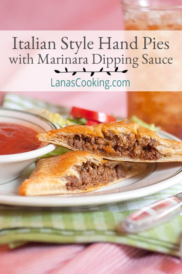Two Italian style hand pies on a plate with a small dish of marinara dipping sauce.