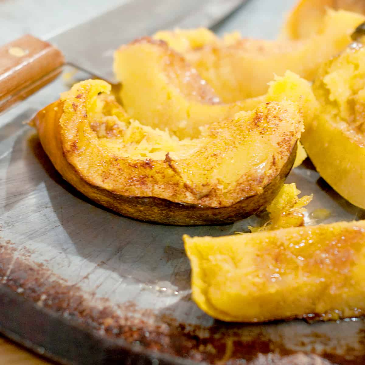 Baked Acorn Squash on a baking sheet with a chef's knife in the background.