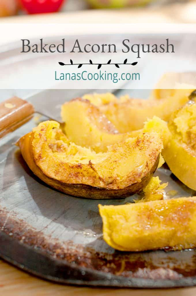 Baked Acorn Squash on a baking sheet with a chef's knife in the background. Text overlay for pinning.