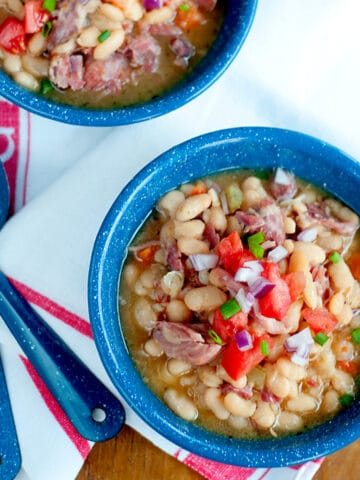 Two bowls of Slow Cooker White Beans with Smoked Ham Hocks presented on a wooden board with a kitchen towel and spoons.