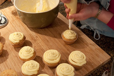 Adding frosting to top of cupcakes with a piping bag.
