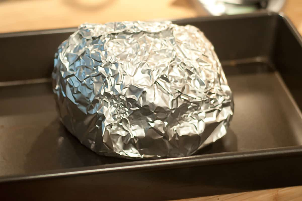 Ham completely wrapped in aluminum foil in a baking pan