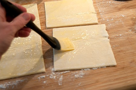 Cut puff pastry into squares and brush with egg wash for Easy Peach Turnovers